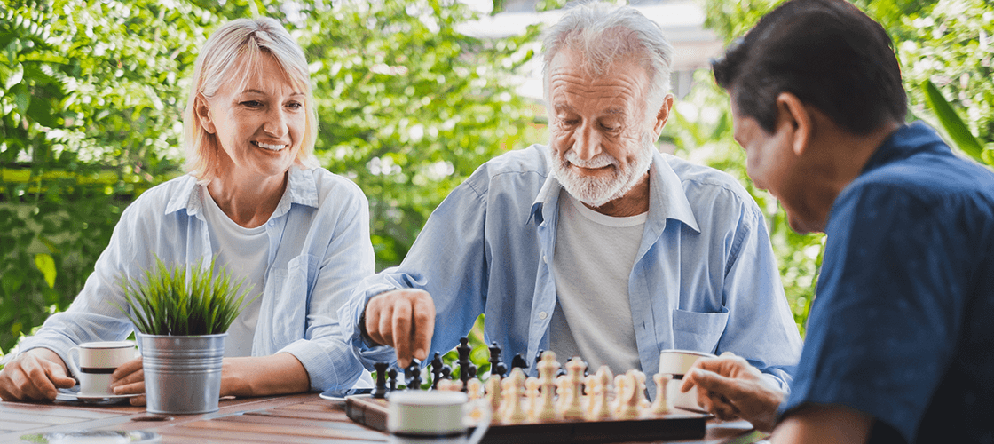Three elderly people playing chess together outside to improve their mental acuity