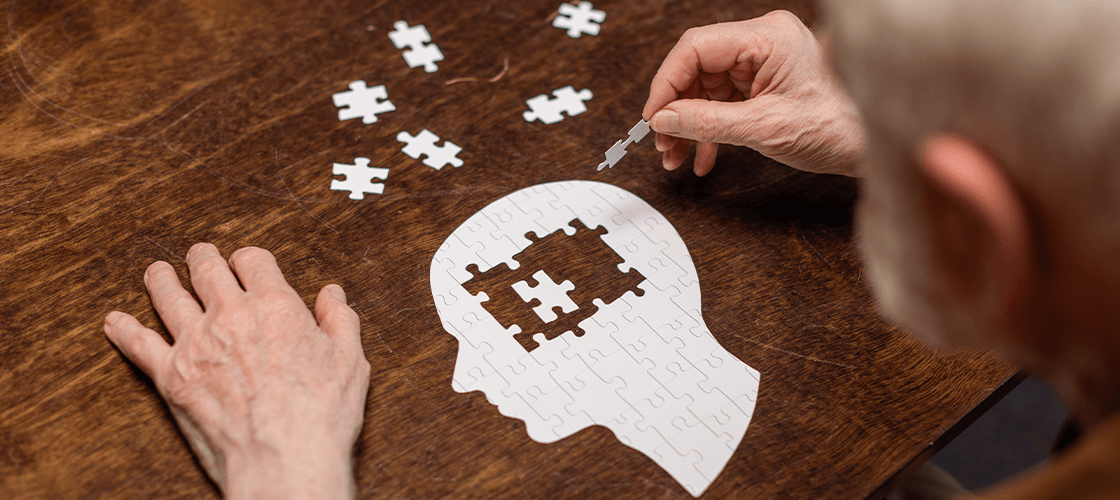 Man sitting at table, sharpening his mind by adding puzzle pieces to a puzzle in the shape of a human head